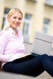 Vrouw die laptop in openlucht met behulp van stock foto's