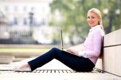 Vrouw die laptop in openlucht met behulp van royalty-vrije stock fotografie