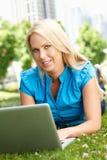 Vrouw die laptop in stadspark met behulp van Royalty-vrije Stock Afbeelding