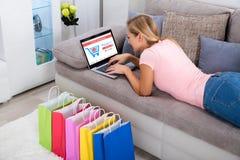 Vrouw die laptop voor online thuis het winkelen met behulp van stock foto