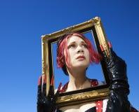Vrouw die leeg frame houdt rond gezicht. royalty-vrije stock afbeelding