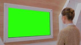 Vrouw die lege groene vertoningsmuur bekijken bij tentoonstelling - groen het schermconcept stock videobeelden