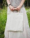 Vrouw die lege linnenzak houden Malplaatjespot omhoog Stock Foto's