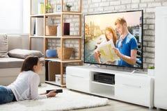 Vrouw die Lettend op Televisie genieten van stock afbeelding