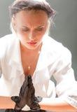 Vrouw die in lichtstraal bidt Stock Afbeeldingen