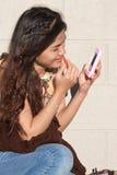 Vrouw die Lippenstift met Telefoon toepast Royalty-vrije Stock Afbeelding