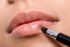 Vrouw die lippenstift op lippen toepast Stock Foto