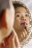Vrouw die lippenstift op lippen toepast Stock Foto's