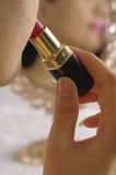 Vrouw die lippenstift op lippen toepast Stock Fotografie