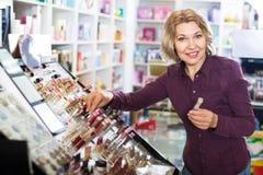 Vrouw die lippenstift in opslag selecteren Stock Foto