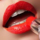 Vrouw die lippenstift toepassen Het model schilderde rode lippen Schoonheidsgezicht met perfecte verse huid Stock Foto
