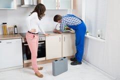 Vrouw die Loodgieter Fixing Sink bekijken royalty-vrije stock afbeelding