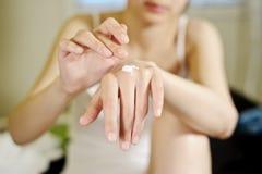 Vrouw die lotion toepast Stock Foto's