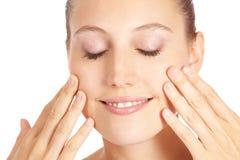 Vrouw die lotion toepast op haar gezicht Stock Fotografie
