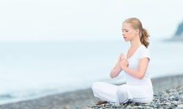 Vrouw die in lotusbloemyoga mediteren op strand stock afbeelding