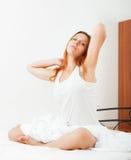 Vrouw die lui op de witte bladen op het bed thuis liggen Royalty-vrije Stock Afbeelding
