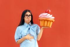 Vrouw die Maag aan Pijn na het Eten van Teveel Cupcake lijden stock afbeelding