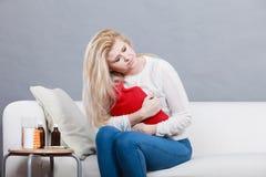 Vrouw die maagklemmen voelen die op cofa zitten Stock Foto