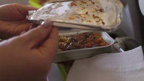 Vrouw die maaltijd op commercieel vliegtuig eten Dienblad van voedsel op het vliegtuig stock footage