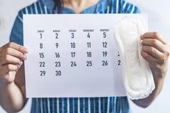 Vrouw die maandelijkse kalender en sanitaire stootkussens houden De kalender van de menstruatiecyclus Het concept van de vrouweng royalty-vrije stock fotografie