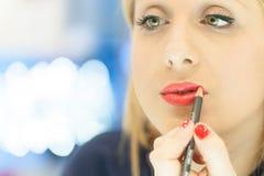 Vrouw die make-up in de spiegel toepassen Stock Afbeeldingen
