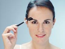 Vrouw die make-up met borstel toepast royalty-vrije stock foto