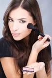 Vrouw die make-up met poederborstel doet Royalty-vrije Stock Foto