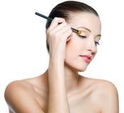 Vrouw die make-up op ogen doet stock afbeeldingen