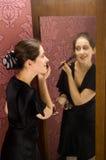 VROUW die MAKE-UP toepast die in de spiegel kijkt Royalty-vrije Stock Foto's
