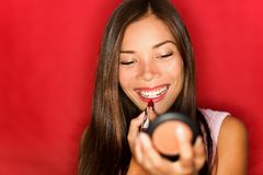 Vrouw die make-uplippenstift zet Stock Foto's