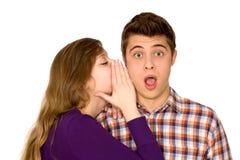 Vrouw die in man oor fluistert Stock Foto