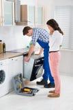 Vrouw die Mannelijke Arbeider bekijken die Oven herstellen stock foto