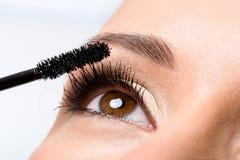 Vrouw die mascara op wimpers toepast Stock Foto