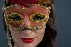 Vrouw die maskerademasker dragen tegen zwarte achtergrond royalty-vrije stock afbeeldingen