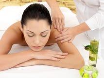 Vrouw die massage van schouder in kuuroordsalon heeft royalty-vrije stock afbeelding