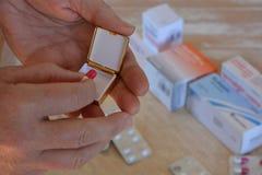 Vrouw die medicijn van een pillendoos nemen stock foto's