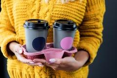 Vrouw die meeneemkoffiekop met model houden stock foto