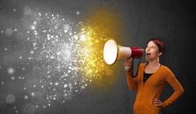 Vrouw die in megafoon en het gloeien explo van energiedeeltjes schreeuwen Stock Foto's
