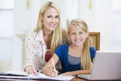 Vrouw die meisje met laptop helpt die thuiswerk doet Royalty-vrije Stock Afbeelding