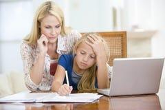 Vrouw die meisje met laptop helpt die thuiswerk doet Stock Afbeelding
