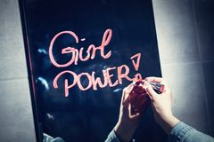 Vrouw die `-meisjesmacht ` op een spiegel met rode lippenstift schrijven stock afbeeldingen