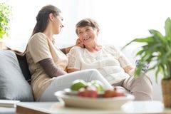 Vrouw die met bejaarde moeder spreken stock afbeeldingen