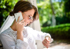 Vrouw die met Celtelefoon neer Horloge bekijken Stock Foto