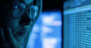 Vrouw die met computer, het binnendringen in een beveiligd computersysteem en het schrijven werken Het computerscherm en code in