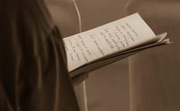 Vrouw die met de hand geschreven nota's lezen bij Dalai Lama-bespreking stock foto's