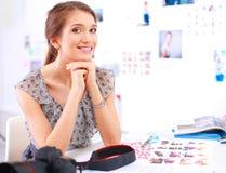 Vrouw die met documenten op het bureau en laptop zitten Stock Afbeelding
