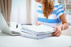 Vrouw die met documenten op het bureau zitten Stock Afbeelding