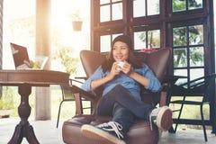 Vrouw die met een koffiekop opheffen, glimlachen die op de laag, bank liggen Stock Fotografie