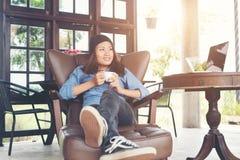 Vrouw die met een koffiekop opheffen, glimlachen die op de laag, bank liggen Stock Afbeeldingen