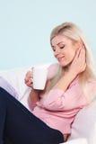 Vrouw die met een mok thee wordt gezeten Stock Foto
